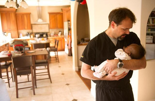 doctor holding baby girl in his home