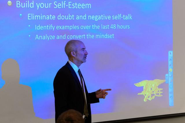 Instructor standing in front of screen addresses students