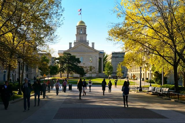 Students walk across the T. Anne Cleary walkway with the Old Capitol in the background.