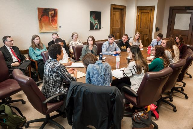 A board room full of middle aged and young adults speaking together over a large table.