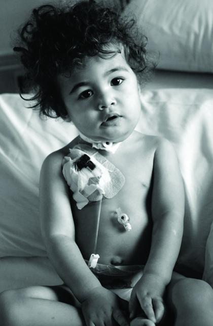 young child sitting in bed with dressing covering insertion site on chest