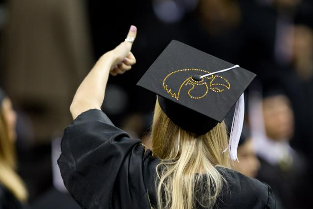 graduate gives a thumbs-up at commencement