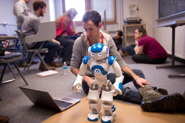 A student works at programming a robot.