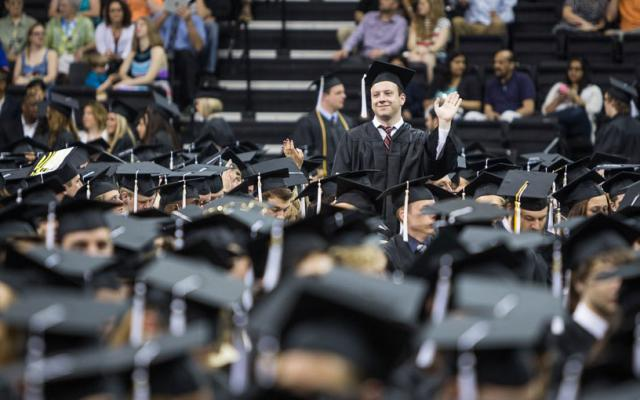 Graduate standing and waving at commencement