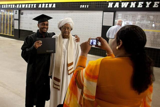 A woman takes a photo of a man in graduation garb alongside an older man.