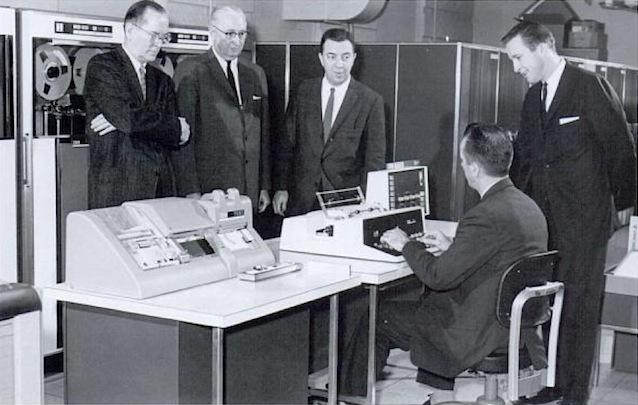 Men in suits standing around an early computer.