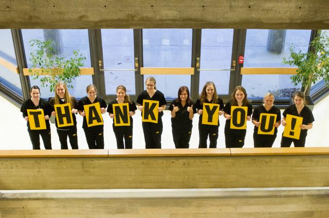 UI College of Nursing students hold up a thank you sign in front of the college.