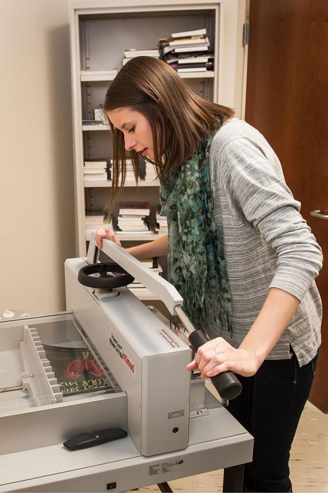 a student at work, cutting a spine of a book in order to scan the pages for accessibility purposes