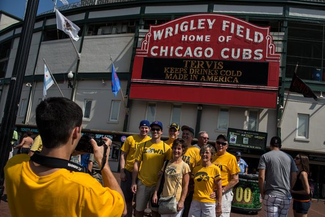 A man in a yellow t-shirt in the bottom left corner takes a photo of a group of people wearing Iowa Hawkeye and Cubs apparel in front of the Wrigley Field marquee.