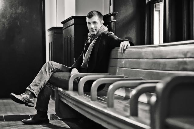 Black-and-white portrait of UI graduate Duncan Wall sitting on a bench