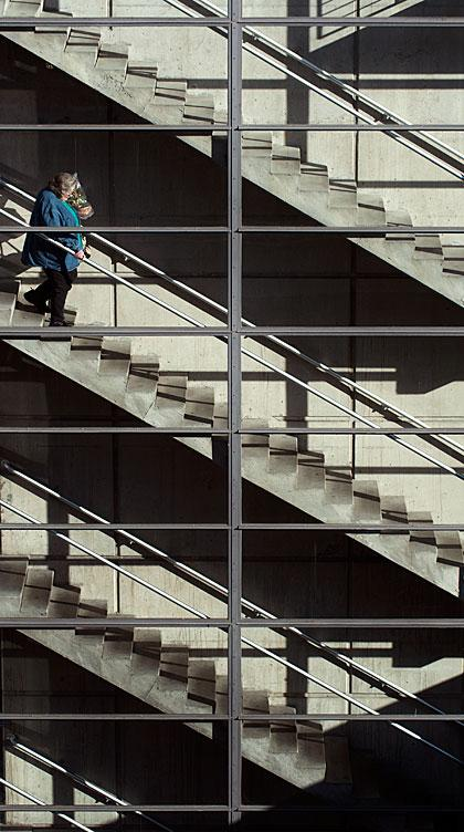 A woman walks down stairs in a hospital parking ramp.