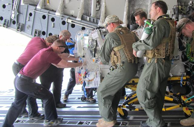 men loading a medical bed into an airplane