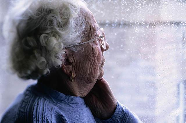 Elderly woman looking out window at rain