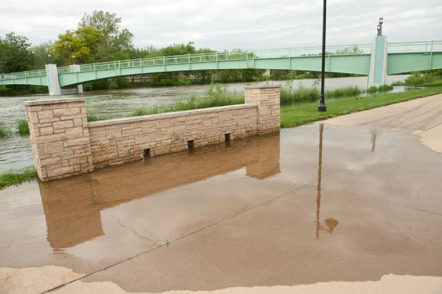 The Iowa River spills onto sidewalk near IMU