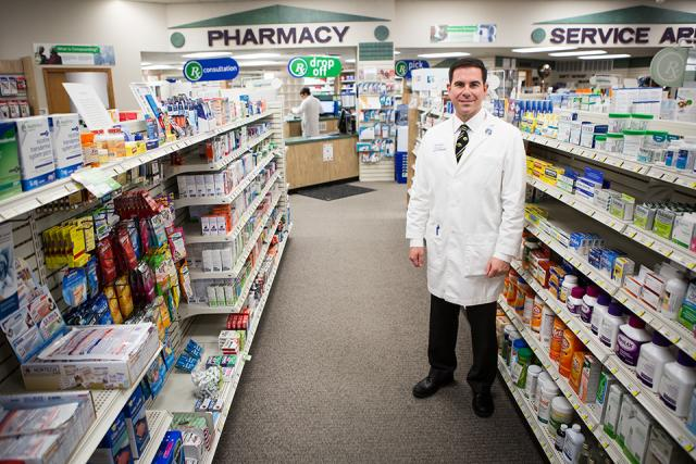 A man in a lab coat and tie standing in the aisle of a pharmacy.