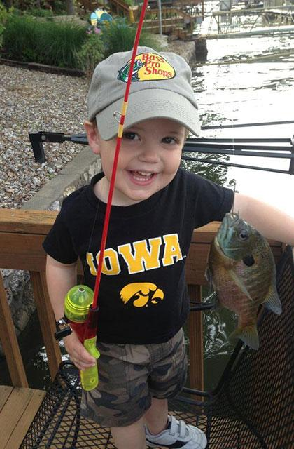 little boy wearing hawkeye shirt holding fishing pole and his fish
