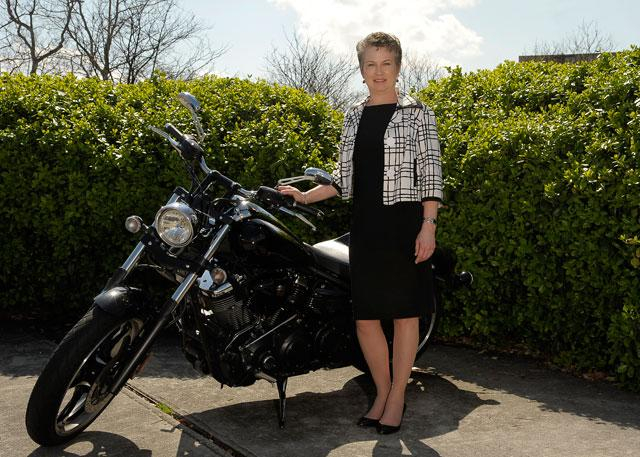 Sarah Gardial stands beside her motorcycle
