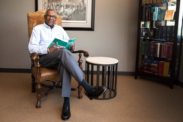 A man sitting in an office holding a book.