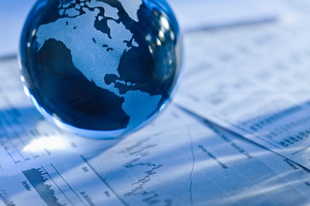 a globe sits on financial papers