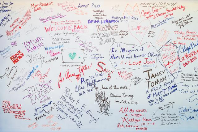 A white background with colored writings, including signatures and drawings made in marker