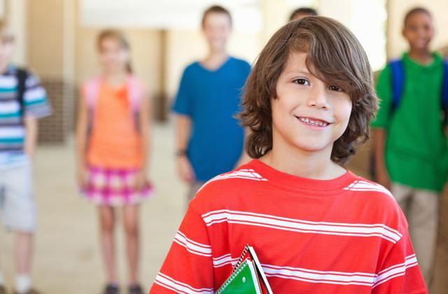 child smiles in school setting, other students stand in background