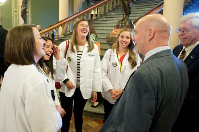Students in white coats chat with a couple of men in suits