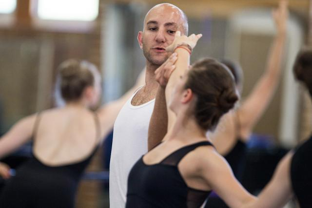 Male dancer holds the arm of a younger female dancer, assisting her ballet form