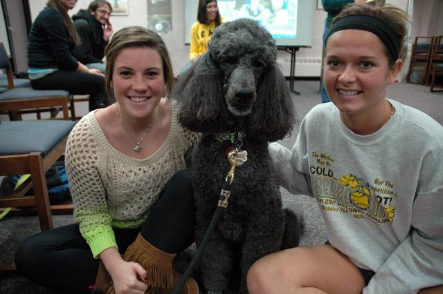 two girls sitting on the floor with a dark gray standard poodle between them