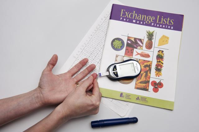Photo illustration showing the use of a blood glucose meter and the recording sheets often used by diabetics.