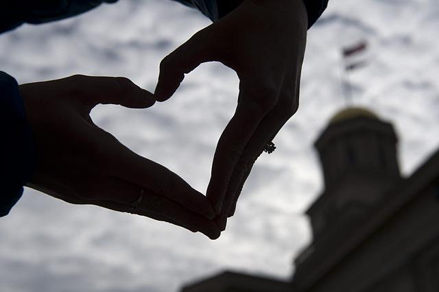 Two hands form a heart with Old Capitol in the background