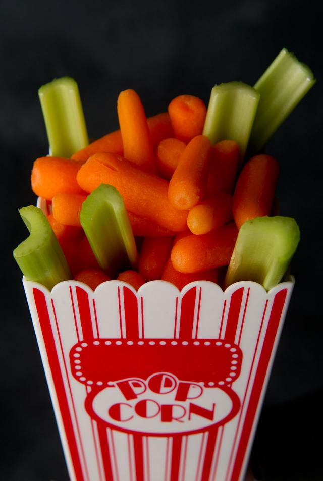 baby carrotts and celery sticks in a popcorn concession tray