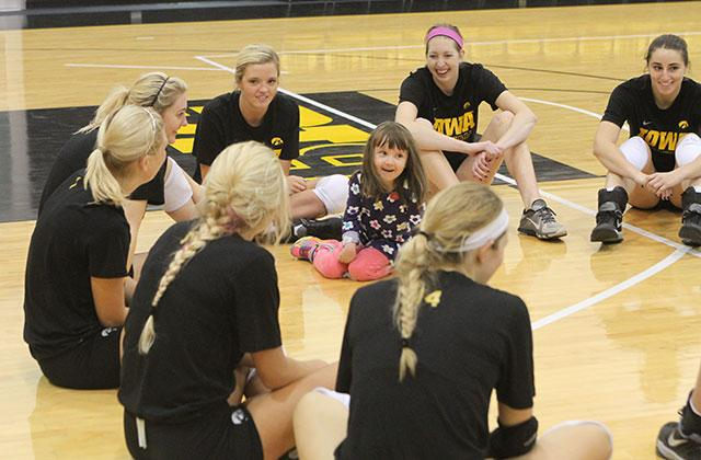 Lucy Jane Roth sits in the middle of a circle of UI volleyball players