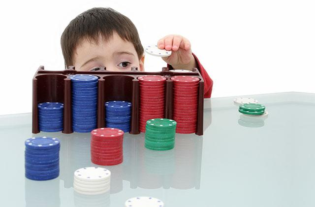 child playing with stack of poker chips