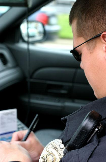 officer seated in car, writing a ticket