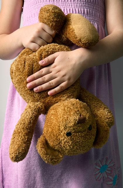 child clutching an upside down teddy bear