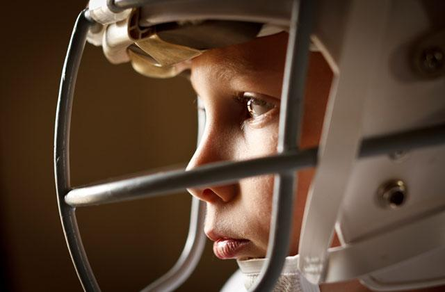 close up of a young boy wearing a football helmet