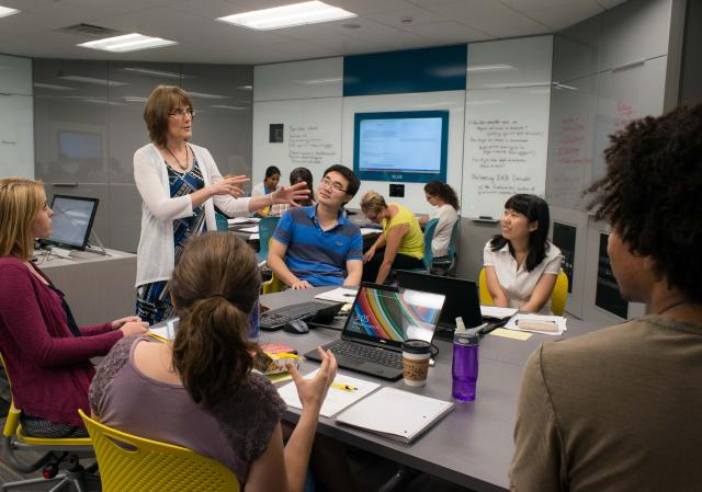 Professor Kathy Schuh leading discussion with a pod of students in N105 classroom.
