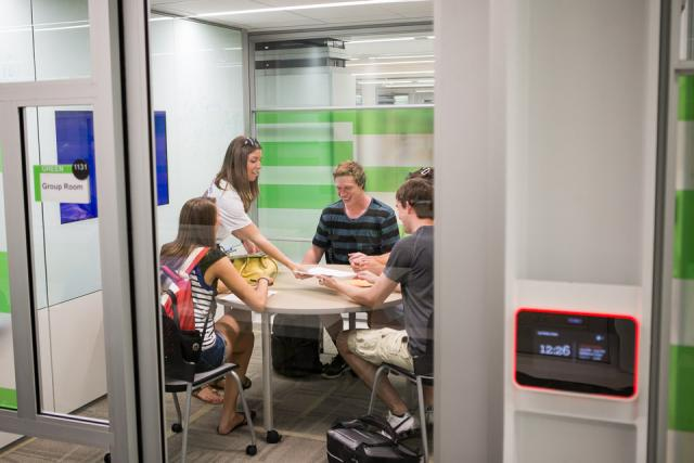 A group of college students talk around a table inside a private room