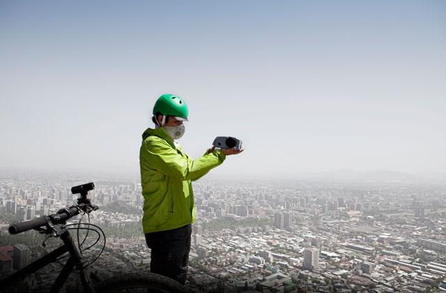 Marcelo Mena-Carrasco is shown standing atop a hill overlooking Santiago with a portable monitoring device to measure levels of particulate matter in the air