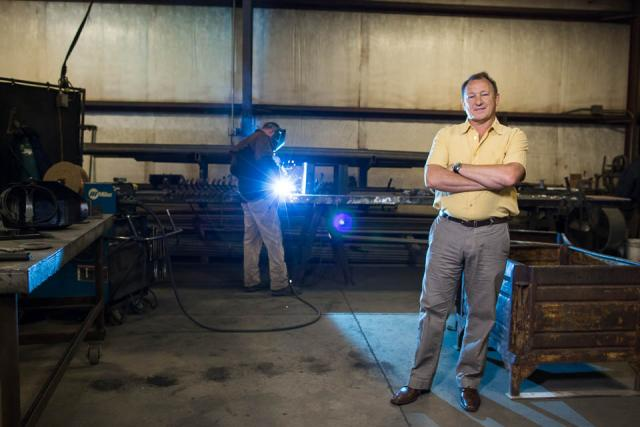 A man posing for a photo in a metal fabrication shop. Another man stands in the background welding a piece of metal with an arc welder.