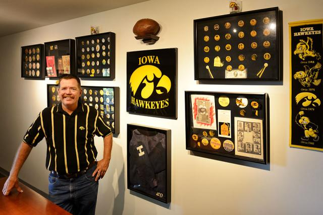 UI graduate Joel Miller shows off his collection of Iowa Homecoming badges and other Hawkeye memorabilia.
