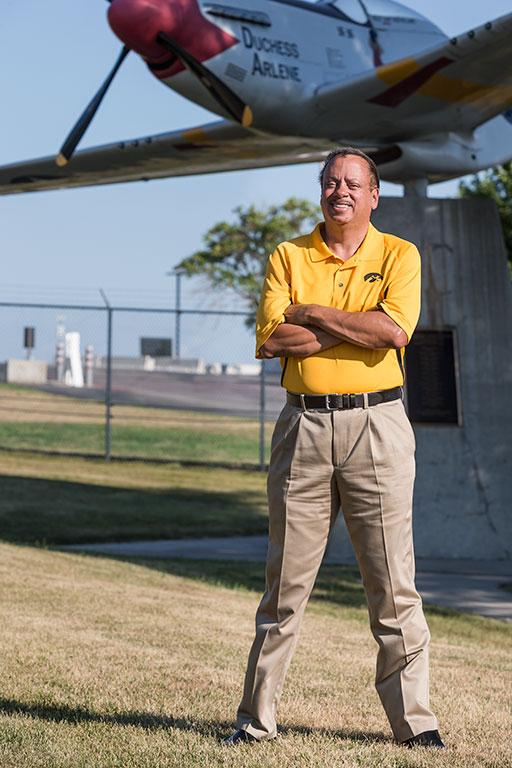 A man posing in front of an airplane.
