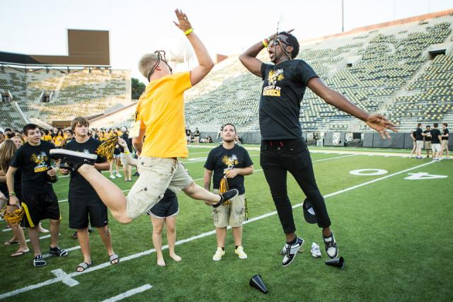 Two young men jump for a high-five on a football field