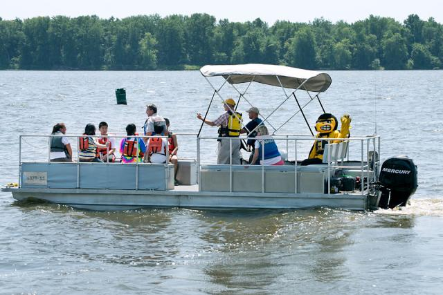 students, researchers, and Herky on pontoon