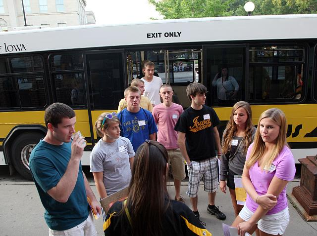 A group of students listens to an orientation guide