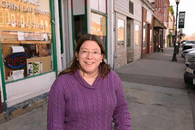 "Cristina ""Nina"" Ortiz poses in front of the Grace Chin Store, a Burmese owned grocery store on Main Street in Columbus Junction."