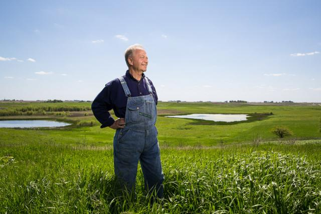 A farmer in bib overalls standing in a field of grass