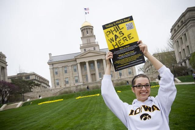 Woman holding up sign in front of Old Capitol