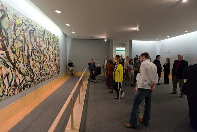 Several people looking at a large painting