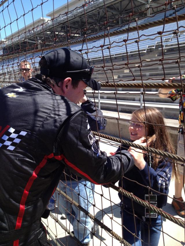 man speaking with daughter at race track